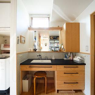 Modelo de aseo asiático con armarios con paneles lisos, puertas de armario de madera oscura, paredes blancas, suelo de madera clara, lavabo integrado, suelo beige y encimeras negras