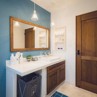 Неиссякаемый источник вдохновения для домашнего уюта: туалет в стиле кантри с фасадами цвета дерева среднего тона, синими стенами, накладной раковиной, столешницей из плитки и бежевым полом