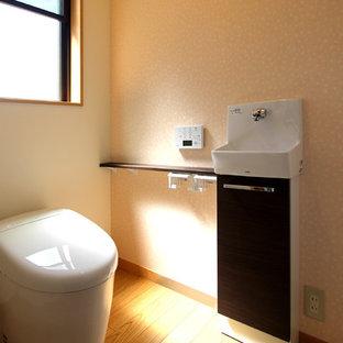 Inspiration för ett litet funkis toalett, med en toalettstol med hel cisternkåpa, rosa väggar, plywoodgolv och beiget golv