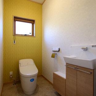 Immagine di un piccolo bagno di servizio moderno con ante a filo, ante bianche, bidè, pareti verdi, pavimento in vinile e pavimento marrone