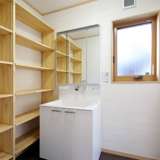 Photo of a small modern cloakroom in Other with beaded cabinets, white cabinets, vinyl flooring and brown floors.