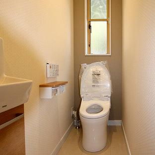 Exemple d'un petit WC et toilettes moderne avec des portes de placard en bois brun, un WC à poser, un mur beige, un sol en contreplaqué et un sol blanc.