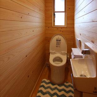 Идея дизайна: маленький туалет в стиле кантри с инсталляцией, бежевыми стенами, полом из фанеры и бежевым полом