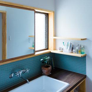 На фото: маленький туалет в скандинавском стиле с синей плиткой, плиткой мозаикой, белыми стенами, накладной раковиной, столешницей из дерева и черной столешницей с