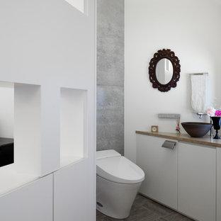 На фото: туалеты в современном стиле с писсуаром, белыми стенами, полом из линолеума, подвесной раковиной, столешницей из дерева, серым полом, плоскими фасадами и белыми фасадами