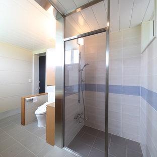 На фото: большие туалеты в современном стиле с фасадами с декоративным кантом, фасадами цвета дерева среднего тона, унитазом-моноблоком, бежевой плиткой, керамогранитной плиткой, бежевыми стенами, полом из керамогранита, монолитной раковиной, столешницей из искусственного камня, серым полом и белой столешницей