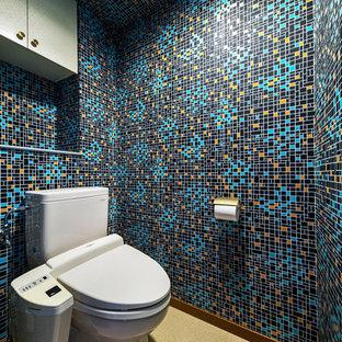 コンテンポラリースタイルのおしゃれなトイレ・洗面所 (マルチカラーの壁、茶色い床、一体型トイレ) の写真