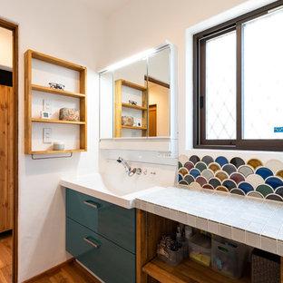 Mittelgroße Country Gästetoilette mit flächenbündigen Schrankfronten, blauen Schränken, Toilette mit Aufsatzspülkasten, weißen Fliesen, Porzellanfliesen, weißer Wandfarbe, dunklem Holzboden, Unterbauwaschbecken, Mineralwerkstoff-Waschtisch, braunem Boden und roter Waschtischplatte in Sonstige