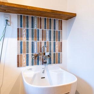 На фото: туалеты среднего размера в восточном стиле с плоскими фасадами, синими фасадами, унитазом-моноблоком, белой плиткой, керамогранитной плиткой, белыми стенами, темным паркетным полом, врезной раковиной, столешницей из искусственного камня, коричневым полом и красной столешницей