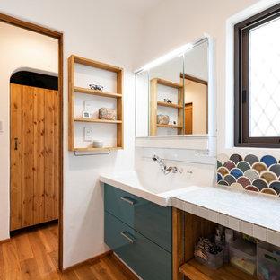Пример оригинального дизайна: туалет среднего размера в восточном стиле с плоскими фасадами, синими фасадами, унитазом-моноблоком, белой плиткой, керамогранитной плиткой, белыми стенами, темным паркетным полом, врезной раковиной, столешницей из искусственного камня, коричневым полом и красной столешницей