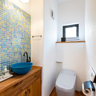 Medium sized rural cloakroom in Other with freestanding cabinets, a one-piece toilet, multi-coloured tiles, mosaic tiles, white walls, dark hardwood flooring, a submerged sink, wooden worktops, brown floors and blue worktops.