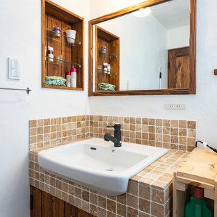 Aménagement d'un petit WC et toilettes méditerranéen avec des portes de placard marrons, un WC à poser, un carrelage beige, un carrelage de pierre, un mur blanc, un sol en bois foncé, un lavabo posé, un plan de toilette en travertin, un sol marron et un plan de toilette beige.
