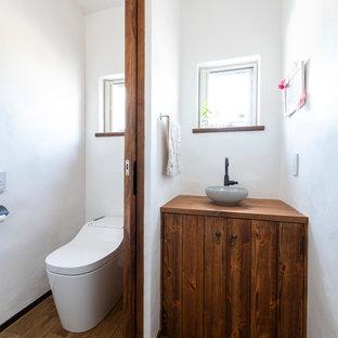 Kleine Mediterrane Gästetoilette mit braunen Schränken, Toilette mit Aufsatzspülkasten, weißer Wandfarbe, dunklem Holzboden, Einbauwaschbecken, Waschtisch aus Holz, braunem Boden und brauner Waschtischplatte in Sonstige