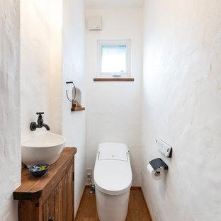 他の地域の小さい地中海スタイルのおしゃれなトイレ・洗面所 (ヴィンテージ仕上げキャビネット、一体型トイレ、白い壁、濃色無垢フローリング、オーバーカウンターシンク、茶色い床) の写真