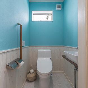 他の地域の北欧風 トイレ・洗面所の画像 (青い壁、ベッセル式洗面器、木製洗面台、白い床、ブラウンの洗面カウンター)