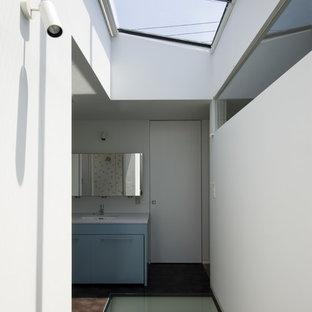 Неиссякаемый источник вдохновения для домашнего уюта: туалет среднего размера в стиле модернизм с плоскими фасадами, бирюзовыми фасадами, белой плиткой, белыми стенами, полом из винила, врезной раковиной, столешницей из искусственного камня, коричневым полом и серой столешницей