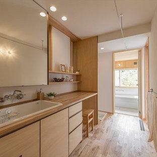 横浜のアジアンスタイルのおしゃれなトイレ・洗面所 (フラットパネル扉のキャビネット、中間色木目調キャビネット、白い壁、無垢フローリング、オーバーカウンターシンク、木製洗面台、茶色い床) の写真