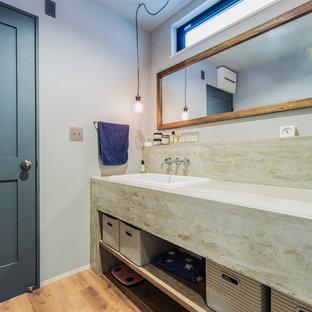 名古屋のビーチスタイルのおしゃれなトイレ・洗面所 (青い壁、淡色無垢フローリング、オーバーカウンターシンク、茶色い床) の写真