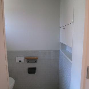 Свежая идея для дизайна: туалет среднего размера в стиле модернизм с фасадами с декоративным кантом, серыми фасадами, унитазом-моноблоком, серой плиткой, керамической плиткой, белыми стенами, полом из керамической плитки, подвесной раковиной, столешницей из плитки, бежевым полом и белой столешницей - отличное фото интерьера