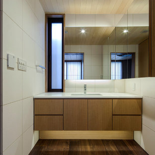 Esempio di un bagno di servizio con ante marroni, piastrelle beige, piastrelle di pietra calcarea, pareti beige, parquet scuro, lavabo sottopiano, top in superficie solida, pavimento marrone e top marrone