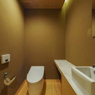 Imagen de aseo asiático con puertas de armario de madera clara, paredes marrones, lavabo sobreencimera, suelo marrón, armarios con paneles lisos y suelo de madera clara