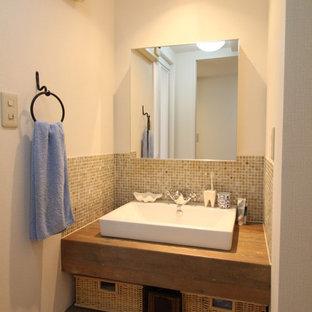 На фото: туалеты в скандинавском стиле с коричневой плиткой, стеклянной плиткой и настольной раковиной