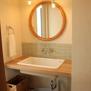 Modelo de aseo de estilo zen con armarios abiertos, baldosas y/o azulejos verdes, baldosas y/o azulejos azules, paredes beige, suelo de madera en tonos medios, lavabo encastrado, encimera de madera, suelo marrón y encimeras marrones