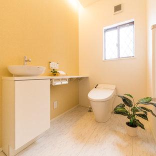 他の地域の広い北欧スタイルのおしゃれなトイレ・洗面所 (黄色い壁、ベッセル式洗面器、ベージュの床) の写真