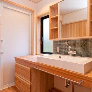 Imagen de aseo de estilo zen con puertas de armario de madera oscura, baldosas y/o azulejos multicolor, paredes blancas, suelo de madera en tonos medios, lavabo sobreencimera, encimera de madera, suelo marrón y encimeras marrones