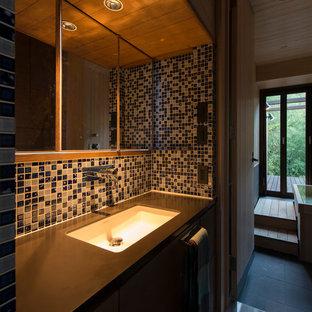 Foto de aseo asiático con armarios con rebordes decorativos, baldosas y/o azulejos azules, suelo de baldosas de cerámica, suelo gris y encimeras marrones