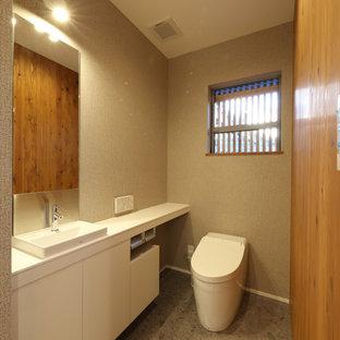 Modelo de aseo de estilo zen, pequeño, con puertas de armario blancas, urinario, paredes beige, suelo de contrachapado, lavabo sobreencimera, encimera de acrílico, suelo gris y encimeras blancas