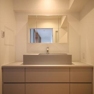 Стильный дизайн: туалет в стиле ретро с плоскими фасадами, серыми фасадами, белыми стенами, полом из фанеры, настольной раковиной, столешницей из ламината, коричневым полом и серой столешницей - последний тренд
