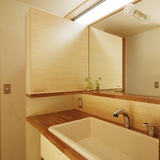 Immagine di un bagno di servizio moderno con ante lisce, ante in legno chiaro, pareti bianche, pavimento in terracotta, lavabo da incasso e top in legno
