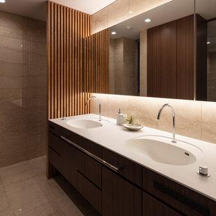 Пример оригинального дизайна: туалет в стиле модернизм с плоскими фасадами, темными деревянными фасадами, бежевыми стенами, мраморным полом, монолитной раковиной и бежевым полом