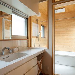 Стильный дизайн: туалет среднего размера в стиле кантри с фасадами с декоративным кантом, белыми фасадами, белой плиткой, белыми стенами, полом из бамбука, врезной раковиной, столешницей из искусственного камня, бежевым полом и белой столешницей - последний тренд