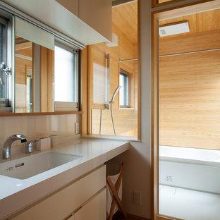 Idées déco pour un WC et toilettes campagne de taille moyenne avec un placard à porte affleurante, des portes de placard blanches, un carrelage blanc, un mur blanc, un sol en bambou, un lavabo encastré, un plan de toilette en surface solide, un sol beige et un plan de toilette blanc.