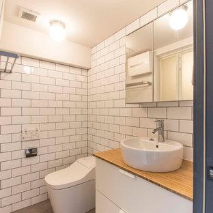東京23区の北欧スタイルのおしゃれなトイレ・洗面所 (フラットパネル扉のキャビネット、白いキャビネット、白いタイル、サブウェイタイル、白い壁、ベッセル式洗面器、木製洗面台、グレーの床、ブラウンの洗面カウンター) の写真