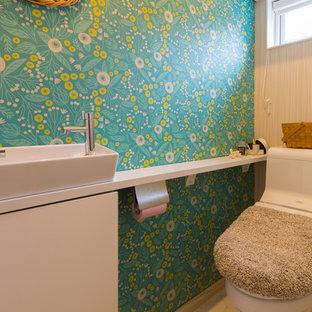 Cette image montre un WC et toilettes nordique de taille moyenne avec un placard à porte plane, des portes de placard blanches, un WC à poser, un mur vert, un sol en linoléum, une vasque, un sol blanc et un plan de toilette blanc.