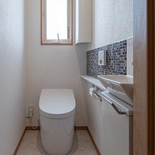 Cette photo montre un WC et toilettes avec un placard à porte plane, des portes de placard blanches, carrelage en mosaïque, un mur blanc, un sol blanc, un plan de toilette blanc, meuble-lavabo encastré, un plafond en papier peint et du papier peint.