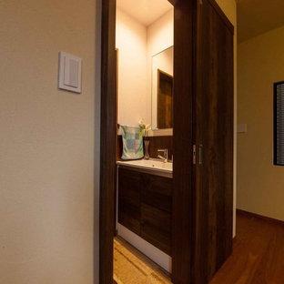 Foto de aseo asiático con baldosas y/o azulejos blancos, paredes marrones, suelo de corcho, lavabo bajoencimera y suelo beige