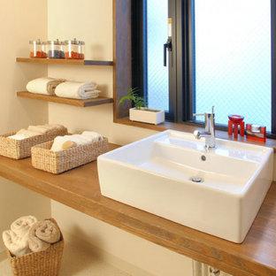 На фото: туалет среднего размера в восточном стиле с открытыми фасадами, фасадами цвета дерева среднего тона, белой плиткой, белыми стенами, полом из линолеума, накладной раковиной, столешницей из дерева, бежевым полом и коричневой столешницей с