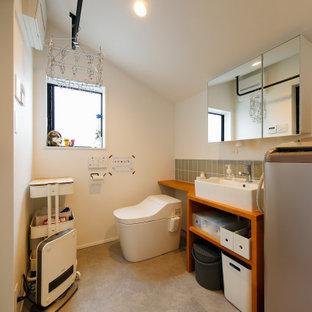 Cette photo montre un WC et toilettes industriel de taille moyenne avec un placard sans porte, des portes de placard marrons, un WC séparé, un carrelage gris, des carreaux de céramique, un mur blanc, un sol en terrazzo, un lavabo encastré, un plan de toilette en bois, un sol beige, un plan de toilette marron, meuble-lavabo encastré, un plafond en papier peint et du papier peint.