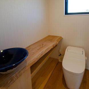 Modelo de aseo de estilo zen, pequeño, con armarios con rebordes decorativos, puertas de armario de madera clara, sanitario de una pieza, paredes blancas, suelo de contrachapado, lavabo sobreencimera, encimera de madera, suelo beige y encimeras azules