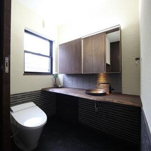 Foto de aseo asiático, de tamaño medio, con armarios tipo mueble, puertas de armario marrones, sanitario de una pieza, baldosas y/o azulejos grises, paredes beige, suelo de baldosas de porcelana, lavabo encastrado, encimera de madera, suelo negro y encimeras marrones