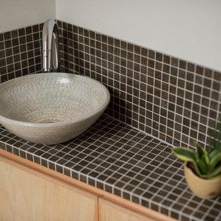 Ispirazione per un bagno di servizio scandinavo con piastrelle nere, lavabo a bacinella e piastrelle di vetro
