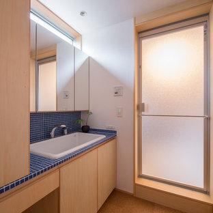 Modelo de aseo de estilo zen con baldosas y/o azulejos azules, lavabo encastrado, encimeras azules, baldosas y/o azulejos de porcelana, suelo de corcho, encimera de azulejos, paredes blancas y suelo marrón