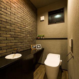 На фото: туалет в стиле модернизм с черными фасадами, унитазом-моноблоком, коричневой плиткой, цементной плиткой, серыми стенами, темным паркетным полом, коричневым полом и черной столешницей с