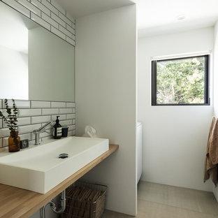 大阪の中くらいのインダストリアルスタイルのおしゃれなトイレ・洗面所 (白いタイル、サブウェイタイル、白い壁、セメントタイルの床、オーバーカウンターシンク、木製洗面台、グレーの床、ブラウンの洗面カウンター) の写真