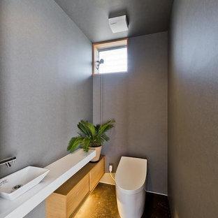 Modelo de aseo de estilo zen con paredes grises, lavabo sobreencimera, suelo negro y encimeras blancas