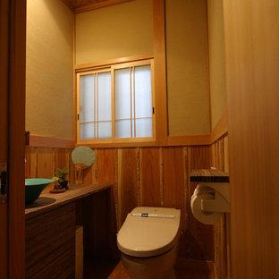 Стильный дизайн: маленький туалет в восточном стиле с плоскими фасадами, темными деревянными фасадами, коричневыми стенами, настольной раковиной, столешницей из дерева, коричневым полом, унитазом-моноблоком, полом из линолеума и коричневой столешницей - последний тренд